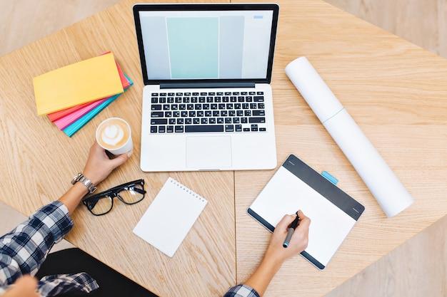 Bovenstaande foto van werkspullen op tafel. handen van jonge vrouw die met laptop werkt, met een kopje koffie. notebooks, zwarte bril, hardwerkend, succes, grafisch ontwerp. Gratis Foto