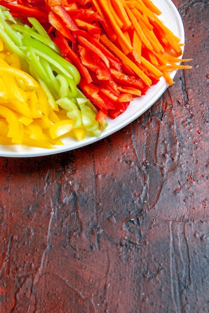 Bovenste helft kleurrijke gesneden paprika's op witte plaat op donkere rode tafel vrije plaats bekijken Gratis Foto
