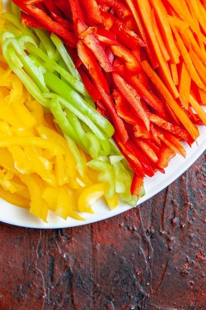 Bovenste helft kleurrijke gesneden paprika's op witte plaat op donkere rode tafel weergeven Gratis Foto