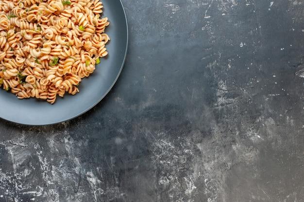 Bovenste helft rotini-pasta op ronde plaat op donkere oppervlak vrije ruimte voedselfoto Gratis Foto