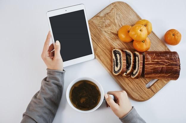 Bovenste schot van vrouwelijke handen die digitale tablet houden terwijl het hebben van ontbijt. slimme vrouw verhoogt de energie met een kopje thee en het eten van mandarijnen met opgerolde cake, een goed gevoel op winterochtend. Gratis Foto