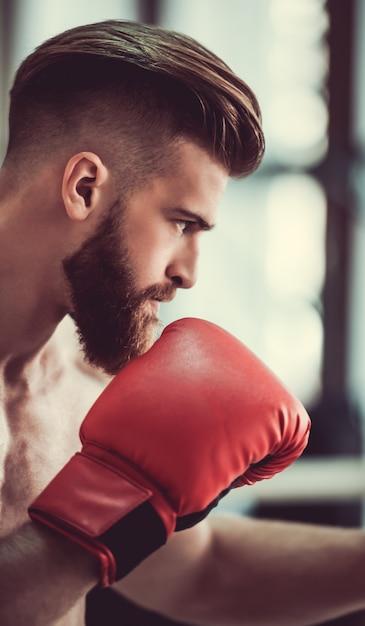 Boxer met blote torso in rode bokshandschoenen klaar om te vechten. Premium Foto