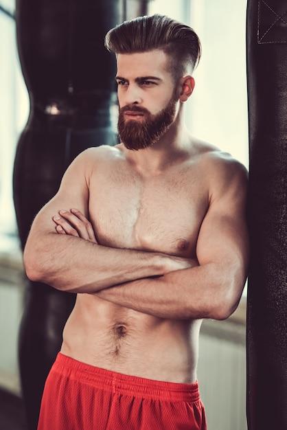 Boxer met blote torso leunt op de bokszak. Premium Foto