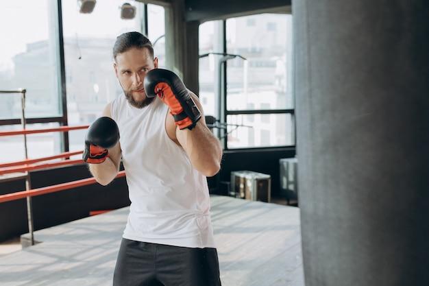 Boxer raakt bokszak in de sportschool in slow motion. jonge man training binnenshuis. sterke atleet in de sportschool Premium Foto