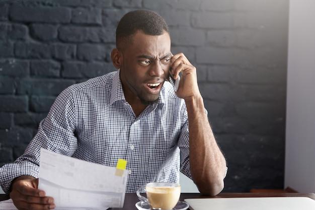 Boze afrikaanse zakenman in formeel overhemd met woedende blik, met stuk papier Gratis Foto
