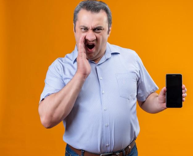 Boze en ontevreden man van middelbare leeftijd in blauw gestreept overhemd schreeuwen en mobiele telefoon tonen Gratis Foto