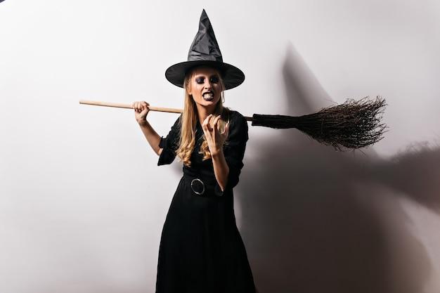 Boze heks die aan iets slechts denkt. vrouwelijke tovenaar in lange zwarte jurk die woede uitdrukt in halloween. Gratis Foto