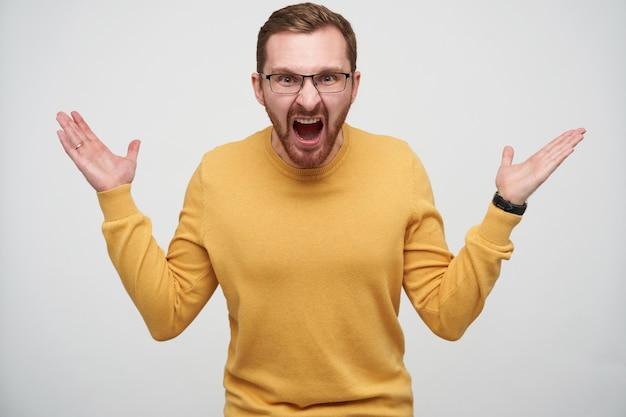 Boze jonge bruinharige bebaarde man in glazen emotioneel palmen opheffen en verhit schreeuwen, staande Gratis Foto