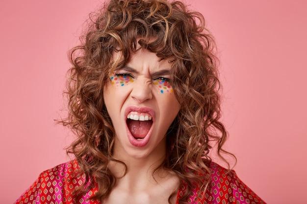 Boze jonge krullende brunette vrouw met feestelijke make-up hevig schreeuwen met brede mond geopend en haar gezicht fronsen, poseren in gekleurde patroon top Gratis Foto