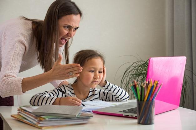 Boze moeder en verveelde dochter tijdens online les Premium Foto