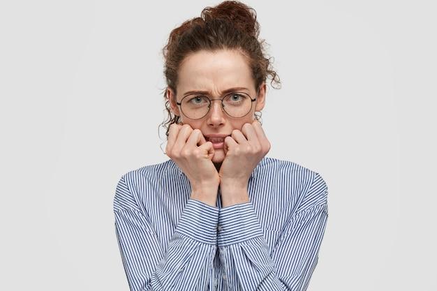 Boze nerveuze vrouw met sproeten bijt vingernagels, kijkt met een norse uitdrukking, ontevreden omdat ze lang moet wachten, gekleed in een gestreept shirt, geïsoleerd over een witte muur. ongenoegen Gratis Foto