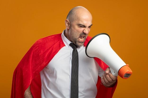 Boze superheldenzakenman die in rode cape aan megafoon schreeuwen die zich over oranje muur bevindt Gratis Foto