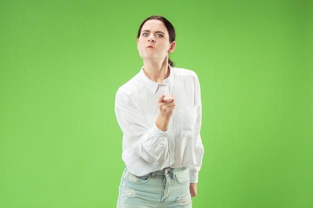 Boze vrouw die camera bekijkt. agressieve zakenvrouw staande geïsoleerd op trendy groene studio achtergrond. Gratis Foto