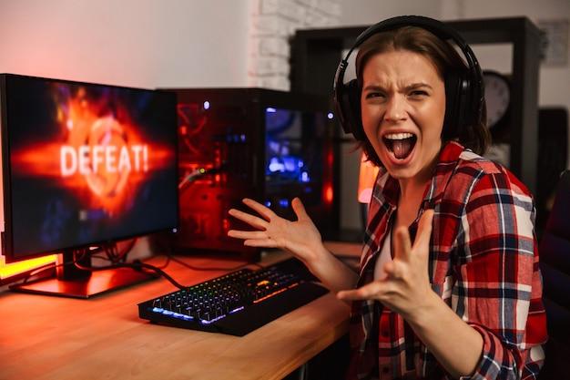Boze vrouw gamer zittend aan tafel, online spelen op een computer binnenshuis Premium Foto