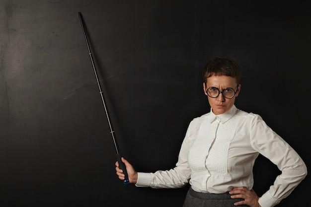 Boze vrouw leraar en shows op zwart krijtbord achter haar met opvouwbare aanwijzer Gratis Foto