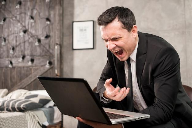 Boze zakenman die bij laptop thuis schreeuwt Gratis Foto