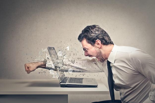 Boze zakenman die zijn laptop verplettert Premium Foto