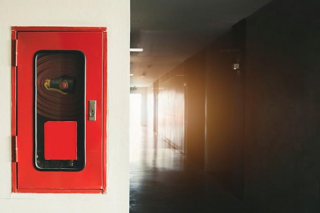 Brandblusapparaat en brandslanghaspel in hotel, brandveiligheidsapparatuur op muurcement Premium Foto