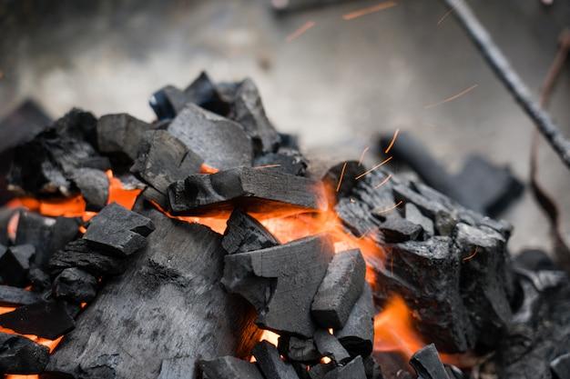 Brandende houtskoolclose-up. kolen in vuur en rook. Premium Foto