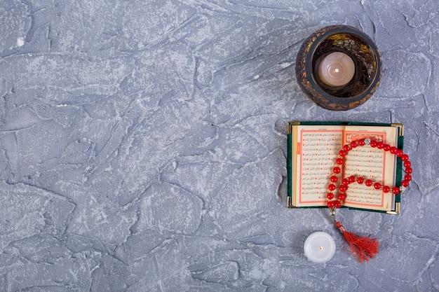 Brandende kaarsen met kuran en rozentuin rode parels op grijze geweven achtergrond Premium Foto