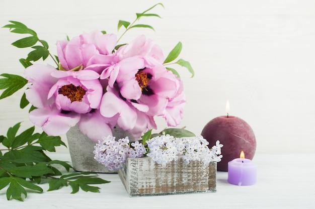 Brandende kaarsen, pioenrozen en lila bloemen Premium Foto