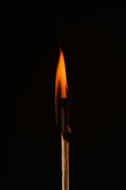 Brandende luciferclose-up op een zwarte. rode vlam. ontsteking matchstick geïsoleerd op zwart. kopieer ruimte. Premium Foto