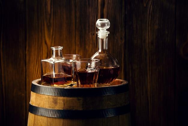 Brandewijn en brandewijn in karaffen staan op een eiken vat, sterke alcoholische dranken in de kelder Premium Foto