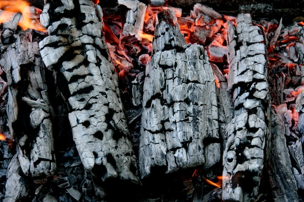 Brandhout branden. smeulende as van een brand. Premium Foto