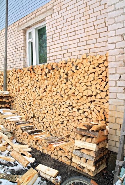 Brandhout in de buurt van muur van het landelijke gebouw Premium Foto