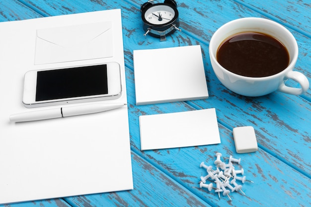 Branding kantoorbehoeftenmodel op blauw bureau. bovenaanzicht van papier, visitekaartje, notitieblok, pennen en koffie. Premium Foto