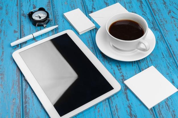 Branding kantoorbehoeftenmodel op blauw bureau. bovenaanzicht van tablet pc, visitekaartje, pad, pennen en koffie. Premium Foto