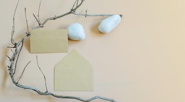 Branding mockup sjabloon met lege envelop, witte stenen en droge boombrunch als natuurlijke elementen op neutrale beige achtergrond. bannerfoto met kopie ruimte, bovenaanzicht, trendy design. Premium Foto