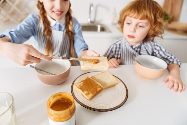 Brandstof voor vandaag. opgewonden vrolijke charmante kinderen die de eerste maaltijd van de dag eten terwijl ze in de keuken zaten voordat ze naar school gingen Premium Foto