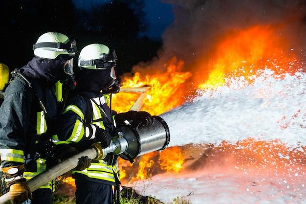 Brandweerman, brandweermannen die een grote brand blussen Premium Foto