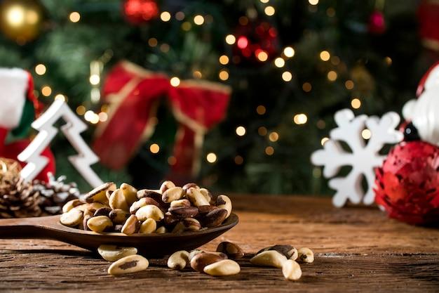Braziliaanse noten: castanha do para in een kom op het bord met onscherpe kerst achtergrond Premium Foto