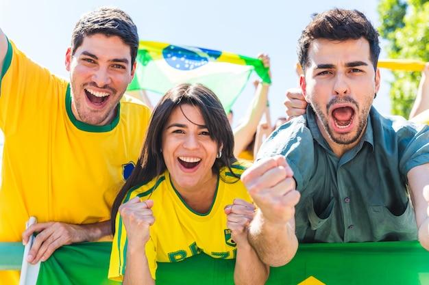Braziliaanse supporters die bij stadion met vlaggen vieren Premium Foto