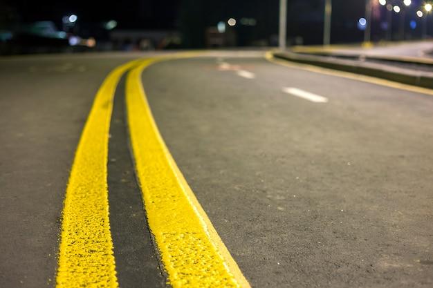 Brede heldere gele straat die tekenlijn langs moderne brede vlotte lege asfaltweg uitrekken die zich aan horizon uitrekken. Premium Foto