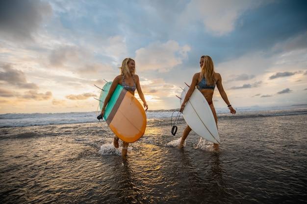 Brede hoek die van twee vrouwen is ontsproten die op het strand met surfplanken lopen Gratis Foto
