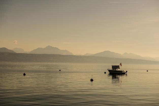 Brede kijkhoek van een boot op het water, omringd door bergen Gratis Foto