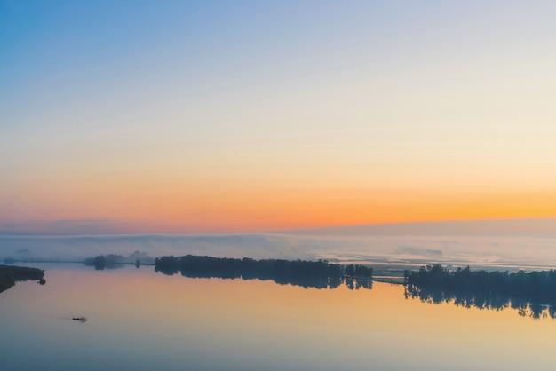 Brede mystieke rivier stroomt langs diagonale kust met silhouet van bomen en dikke mist. gouden gloed in predawnhemel. rustig ochtend sfeervol landschap van majestueuze natuur in warme tinten. Premium Foto