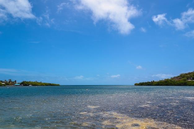 Brede opname van een prachtig uitzicht op de oceaan met een bewolkte blauwe hemel Gratis Foto