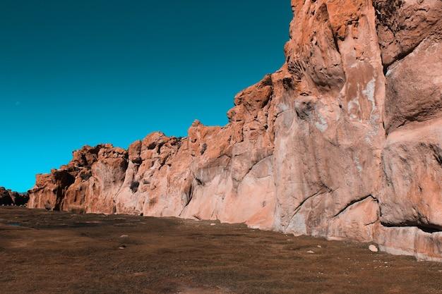 Brede opname van kliffen omgeven door land met een blauwe lucht op een zonnige dag Gratis Foto