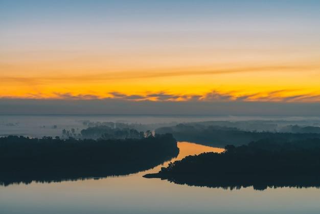 Brede rivier stroomt langs de kust met bos onder dikke mist. Premium Foto