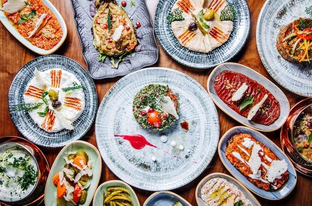 Brede selectie van oosterse, oosterse gerechten in rustieke borden op tafel. Gratis Foto