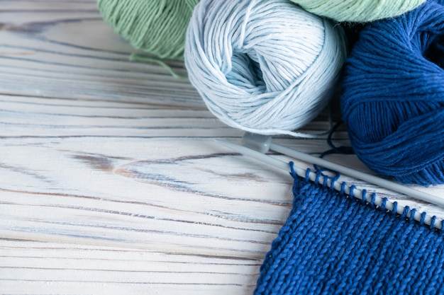 Breiende hobbysamenstelling met blauw en groen garen en naalden op witte houten Premium Foto