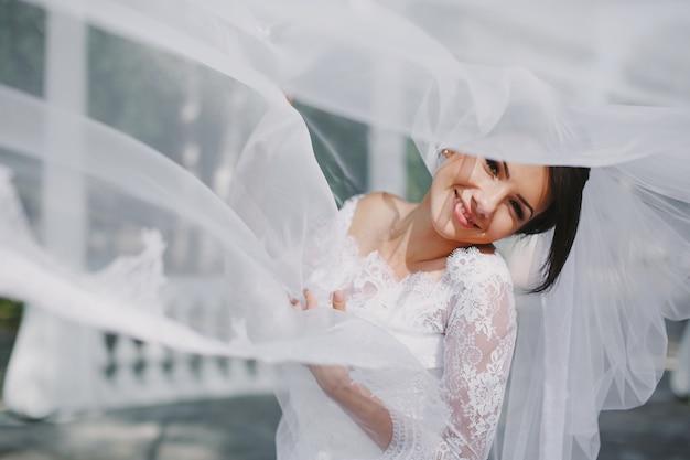 Bride lachend door de sluier Gratis Foto