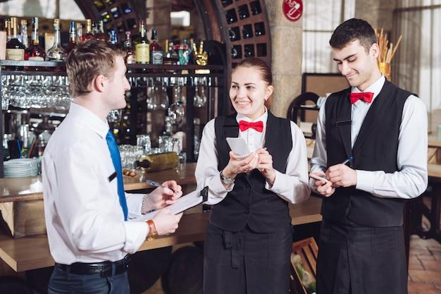 Briefing van de manager met de obers. restaurantmanager en zijn personeel. Premium Foto