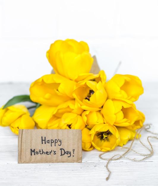 Briefkaart moederdag en gele tulpen op houten Gratis Foto