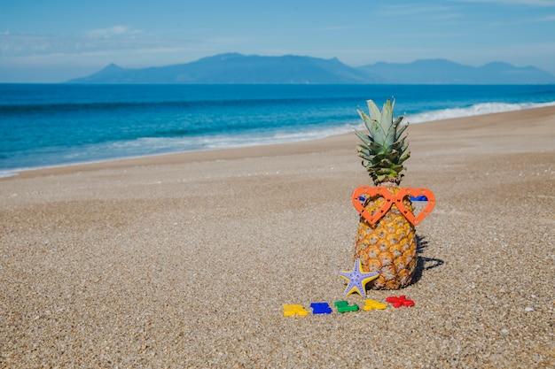 Brieven en ananas in het strand Gratis Foto