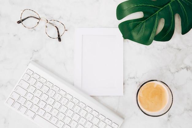 Bril; koffie glas; monster blad en fotolijst met toetsenbord op witte marmeren gestructureerde achtergrond Gratis Foto